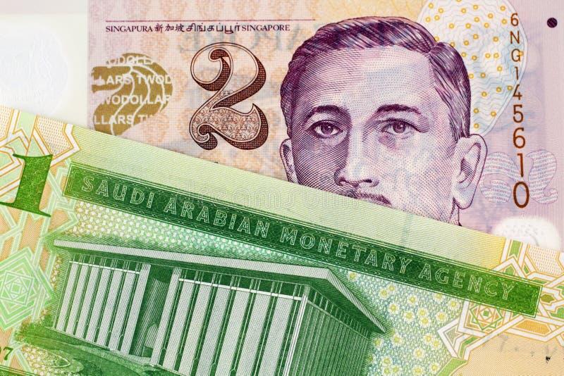 En Riyalsedel för en saudier med en dollarsedel för två Singapore arkivfoton