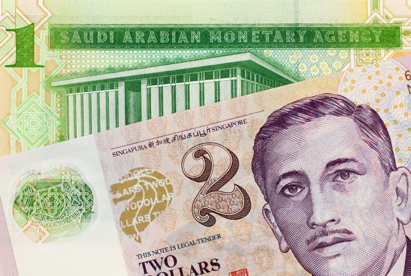 En Riyalsedel för en saudier med en dollarsedel för två Singapore arkivfoto