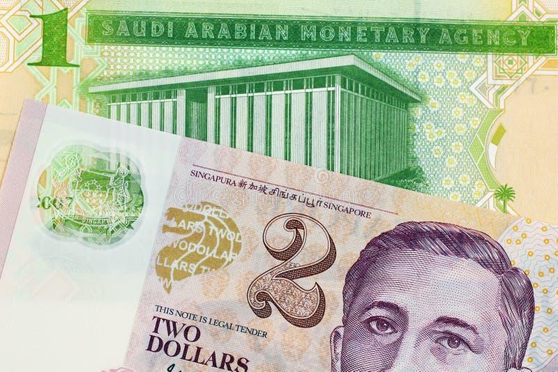En Riyalsedel för en saudier med en dollarsedel för två Singapore royaltyfri fotografi