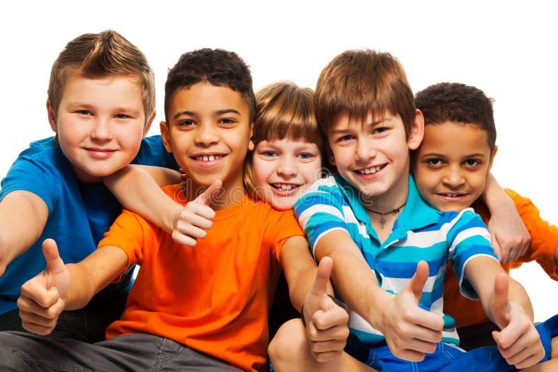 En ro av fem lyckliga ungar royaltyfri foto