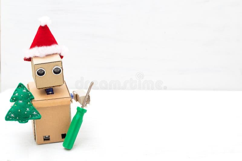 En robot i en santa hatt rymmer en julgran och en skruvmejsel C fotografering för bildbyråer