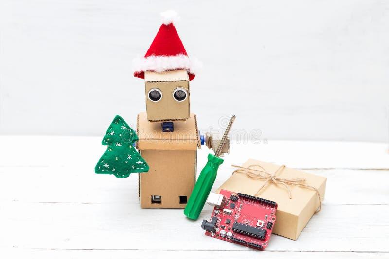 En robot i en santa hatt rymmer en leksak av julträdet och screwdr royaltyfri bild