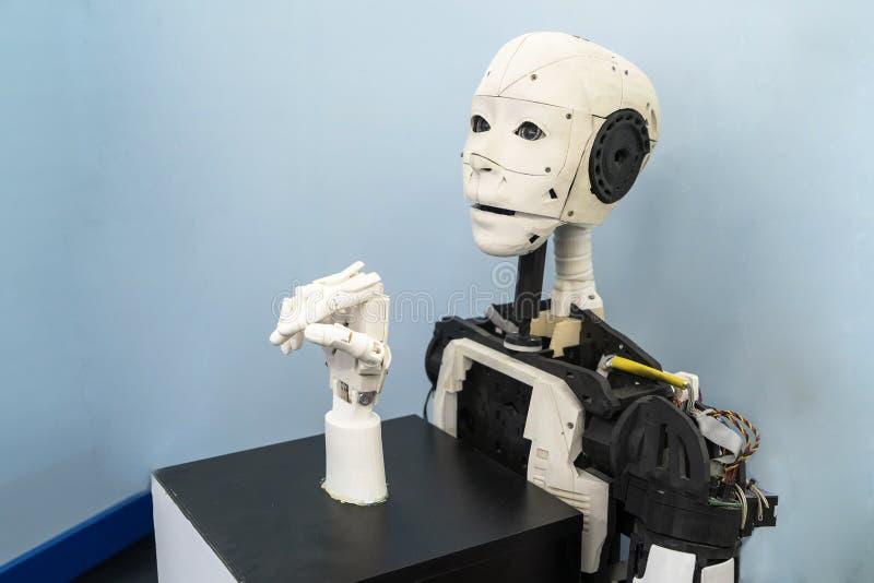 En robot med en mänsklig framsida, en mekanisk arm, en bionisk arm Utställning på robotteknik-Robostjärnor en festival av robotar royaltyfri fotografi