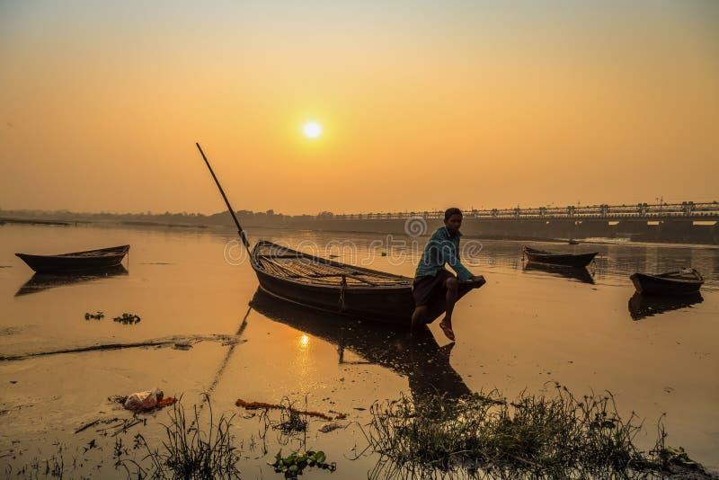 En roddare sitter på hans fartyg för att stötta på solnedgången på floden Damodar nära det Durgapur dammet arkivbild