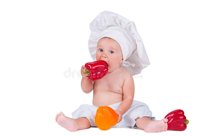 En rolig liten flicka i kläder för kock` ett s äter peppar arkivfoto