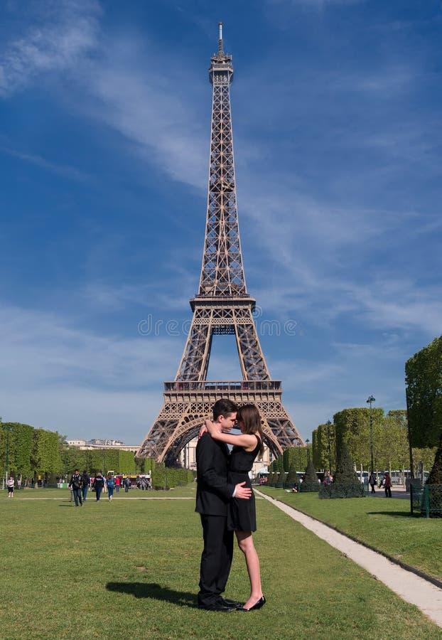 En romantisk ung parkram tillsammans framme av den Eiffel Tower〠'en, royaltyfri bild