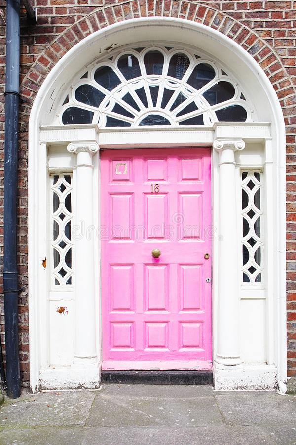 En rosa dörr i Dublin, Irland Arched Georgian door Front i Dublin fotografering för bildbyråer