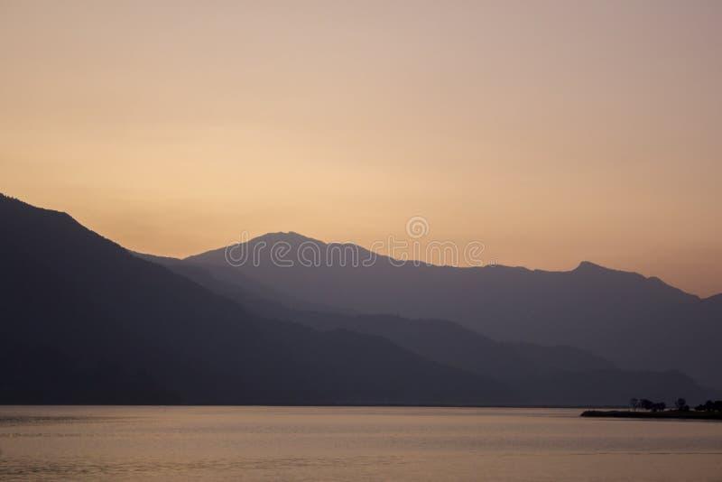 En rosa grå solnedgånghimmel över sjöarna mot de svarta konturerna av bergen royaltyfri foto