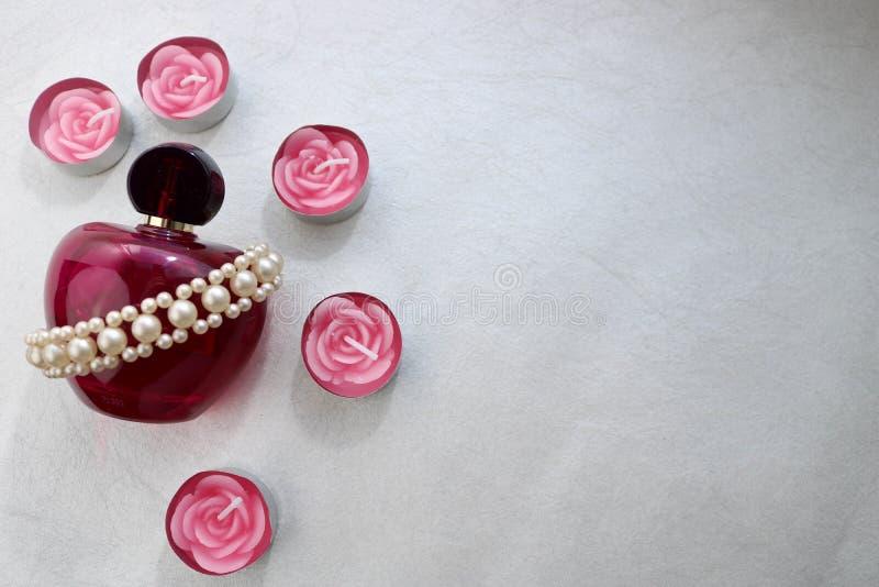 En rosa härlig glass genomskinlig flaska av kvinnlig doft smyckade med vita gråbruna pärlor och rosa paraffinstearinljus i formen arkivfoton
