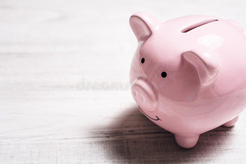 En rosa le Piggybank på en tabell royaltyfria foton