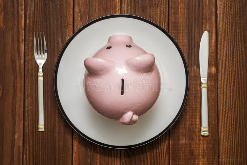 En rosa spargris på maträtt Besparingkonsumentbegrepp Spargris på plattan med gaffeln och kniven finansiellt begrepp arkivbild