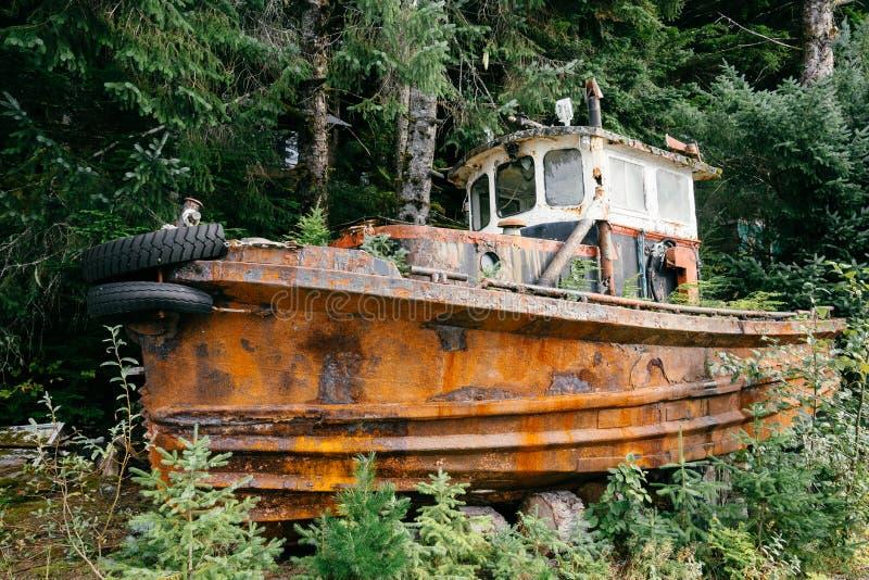 En rostig övergiven fiskebåt vid träd royaltyfria bilder