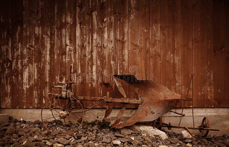 En rostig gammal hästplog framme av en riden ut träladugårdvägg i den bruna färgsignalen för en västra blick arkivfoto