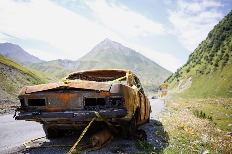 En rostig utbränd bil med inga baklyktor på vägen i bergen arkivfoton
