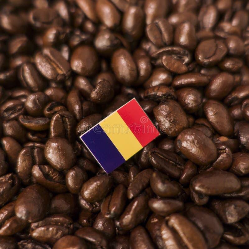 En Rumänien flagga som förläggas över grillade kaffebönor royaltyfri bild