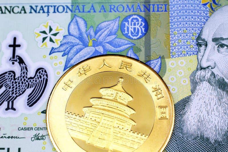 En en rumänsk leu med ett kinesiskt ett guld- mynt för uns arkivfoto