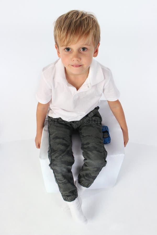 En säker le barnpojke som sitter på en kub och ser upp royaltyfri foto