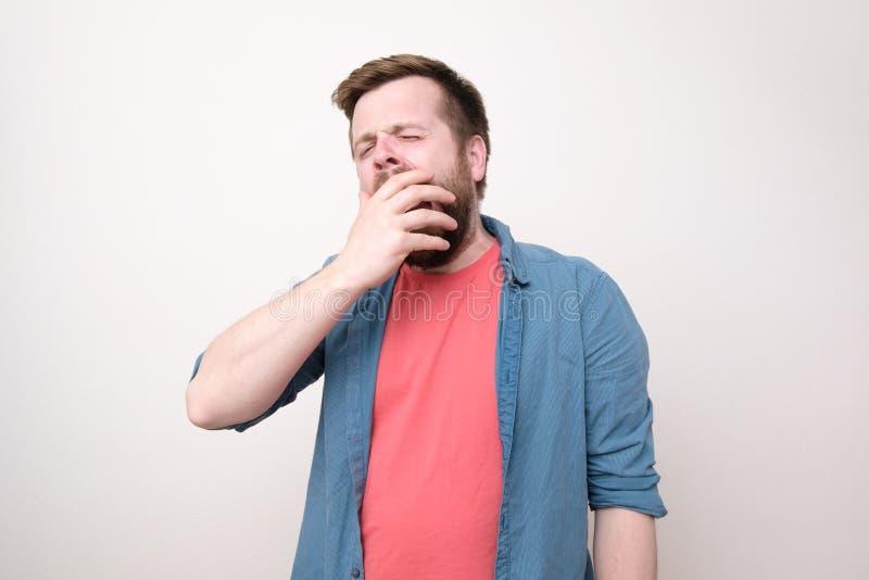 En s?mnig ung europeisk man med ett sk?gg, g?spar och t?cker hans mun med hans hand P? vitbakgrund royaltyfri fotografi