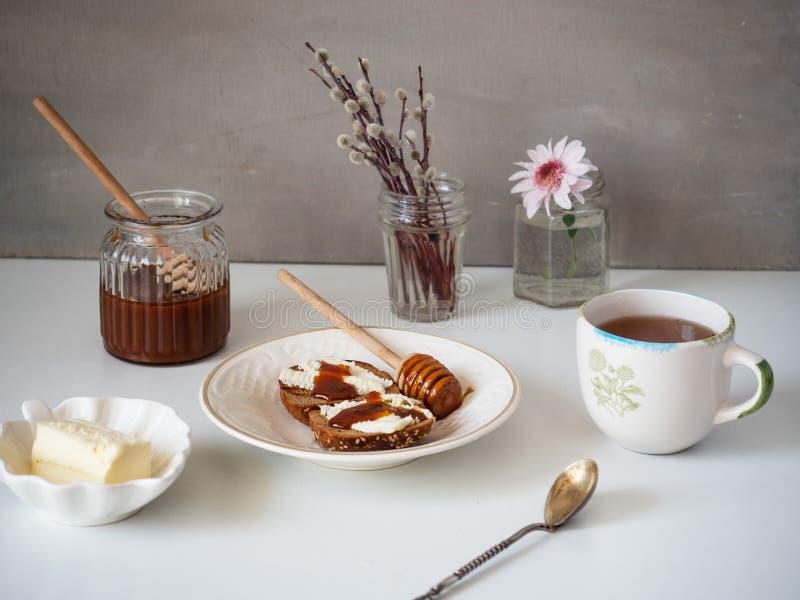 En söt lunch av smörgåsar med smör och honung och te på en vit tabell Honung i en exponeringsglaskrus, blommor i små vaser arkivbild