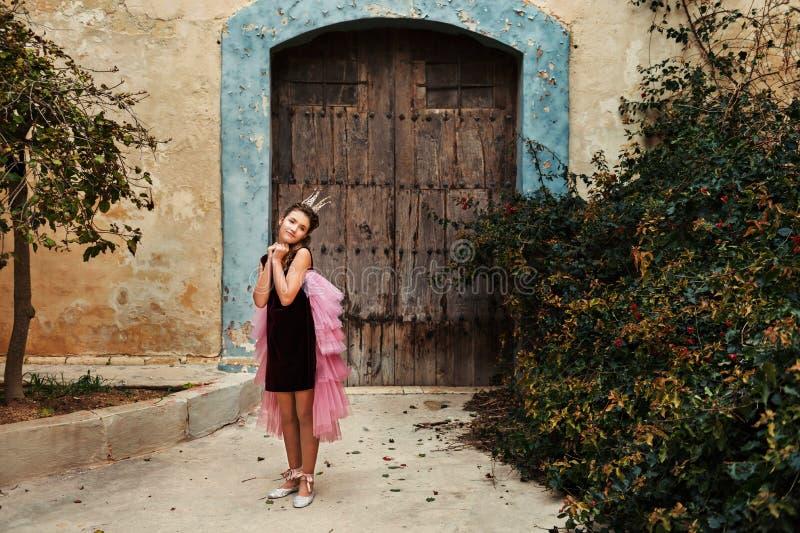 En söt prinsessaflicka i en krona och en burgundy klänning med en rosa färg skyler skämmas bort framme av ett gammalt hus med ett royaltyfria bilder