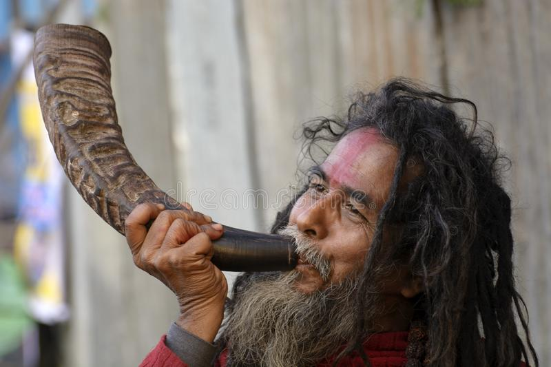 En sadhu eller en munk som spelar Singha, genom att blåsa den i Gangaen Sagar Mela i Kolkata arkivbilder