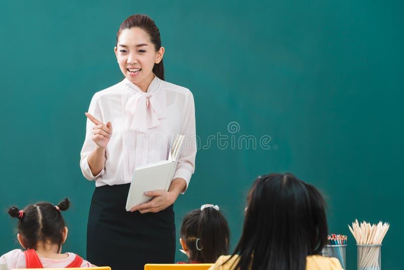 En sala de clase, el profesor asiático enseña al estudiante imagenes de archivo