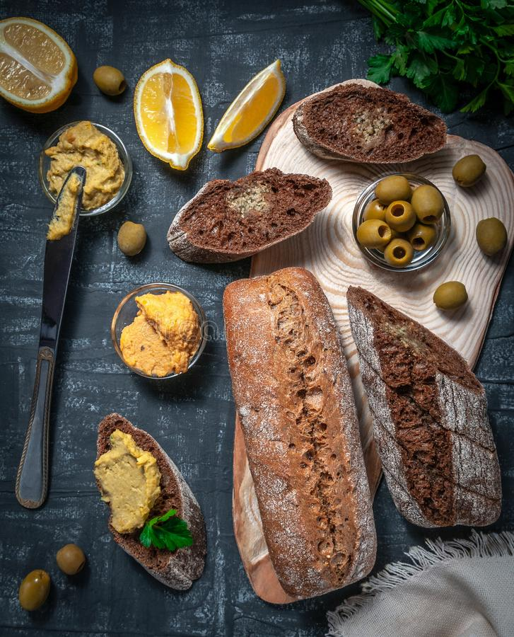 En sammansättning av två bagetter av kli och helt kornmjöl Smörgås av hummusen och oliv På trämellanrummet Sikt från arkivbild