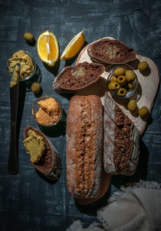 En sammansättning av två bagetter av kli och helt kornmjöl Smörgås av hummusen och oliv På trämellanrummet Sikt från royaltyfri foto