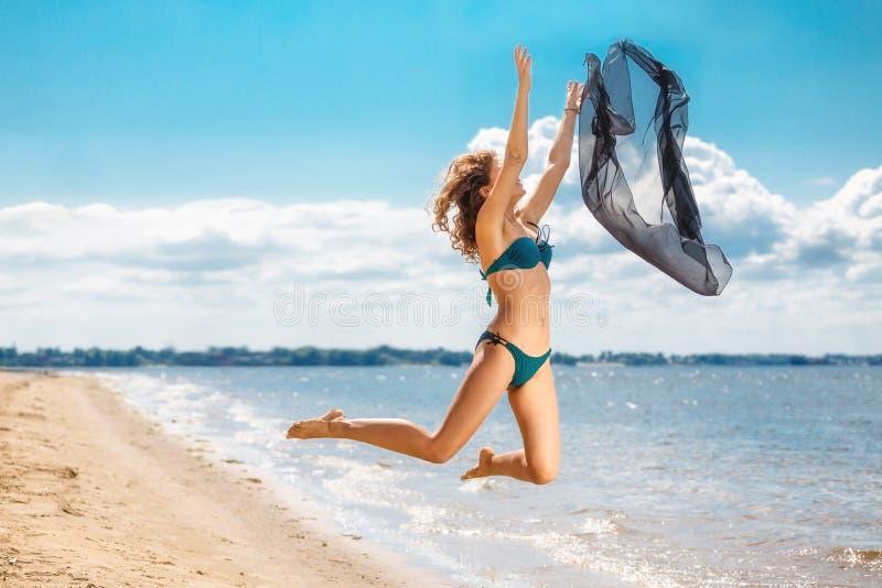 En sautant la fille heureuse sur la plage, adaptez le corps sexy sain sportif dans le bikini images stock