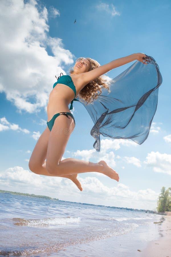 En sautant la fille heureuse sur la plage, adaptez le corps sexy sain sportif dans le bikini photos stock