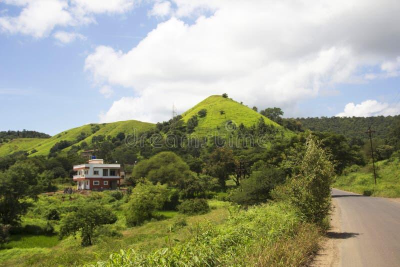En scenisk sikt med bunglow, den frodiga gröna kullen och vägen under monsun, Mandvi Khurd, Pune område royaltyfria bilder