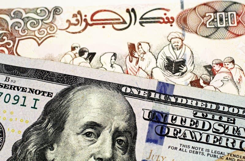 En sedel för algerisk dinar tvåhundra med en amerikansk hundra dollarräkning arkivfoto