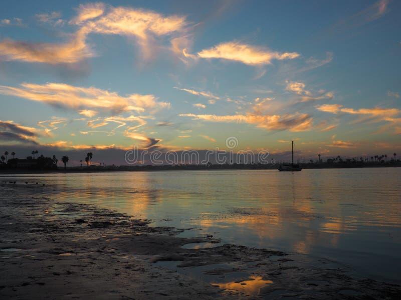 En segelbåt driver under solnedgång på stranden fotografering för bildbyråer