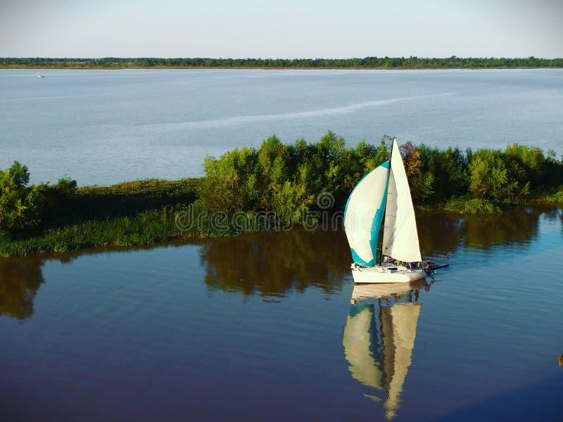 en segelbåt och dess reflexion i den Paranà ¡ floden på solnedgången arkivbild