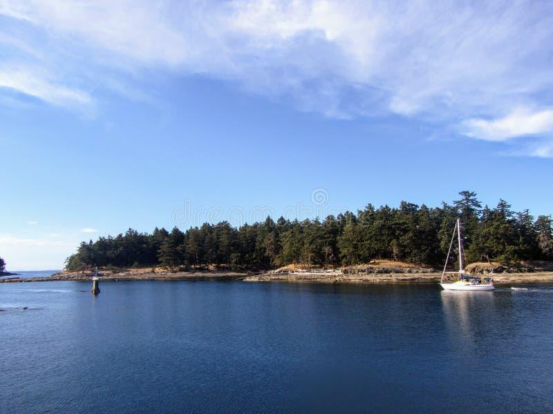En segelbåt som navigerar försiktigt en passage med rever i golföarna, British Columbia, Kanada royaltyfria foton
