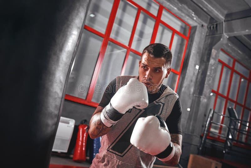 En sekund för Focused tatuerade idrottsman nen i sportar som beklär boxning på tung stansmaskinpåse, medan öva i boxningen royaltyfri bild