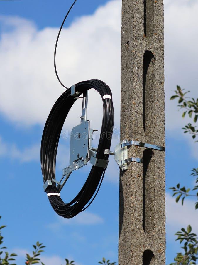En sele för optisk kabel för fiber för kommunikation väger på en konkret kolonn Telekommunikationer och internet Reparationsarbet royaltyfri foto