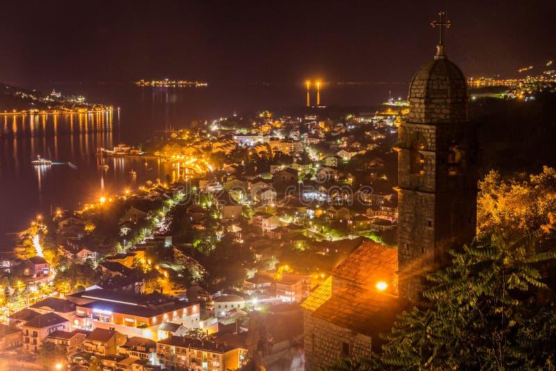 En sen afton på den Kotor fjärden, tände en gammal stad vid orange ljus royaltyfria foton