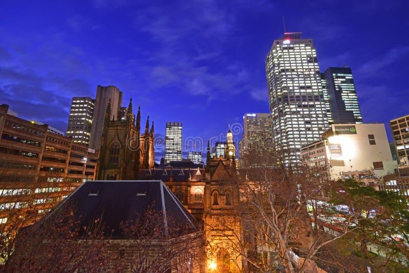 En sen afton tidigt nattlandskap av att blänka Sydney CBD runt om townhallområde som tas från takbyggnad royaltyfria foton