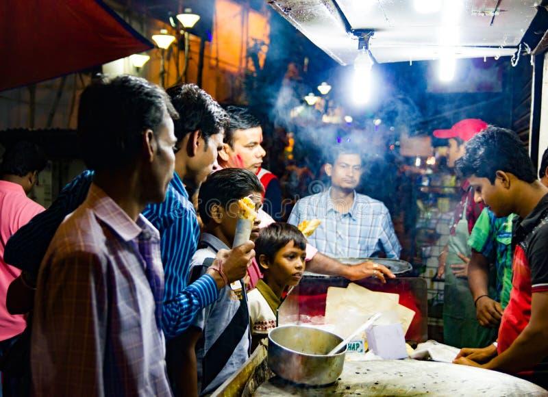 En septiembre de 2017, Kolkata, la India Clientes que compran rollo de huevo en una parada en kolkata en la noche foto de archivo libre de regalías