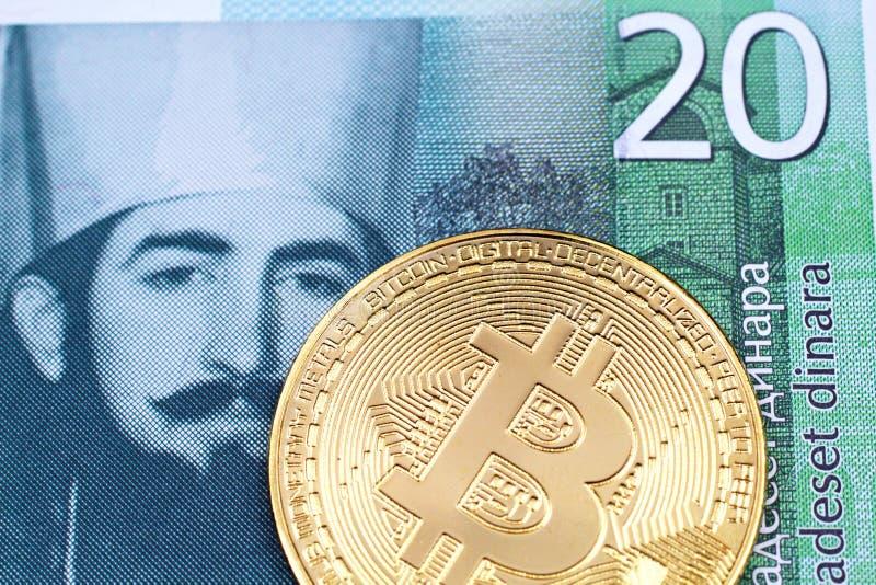 En serbisk sedel för dinar tjugo med en guld- fysisk bitcoin arkivbild