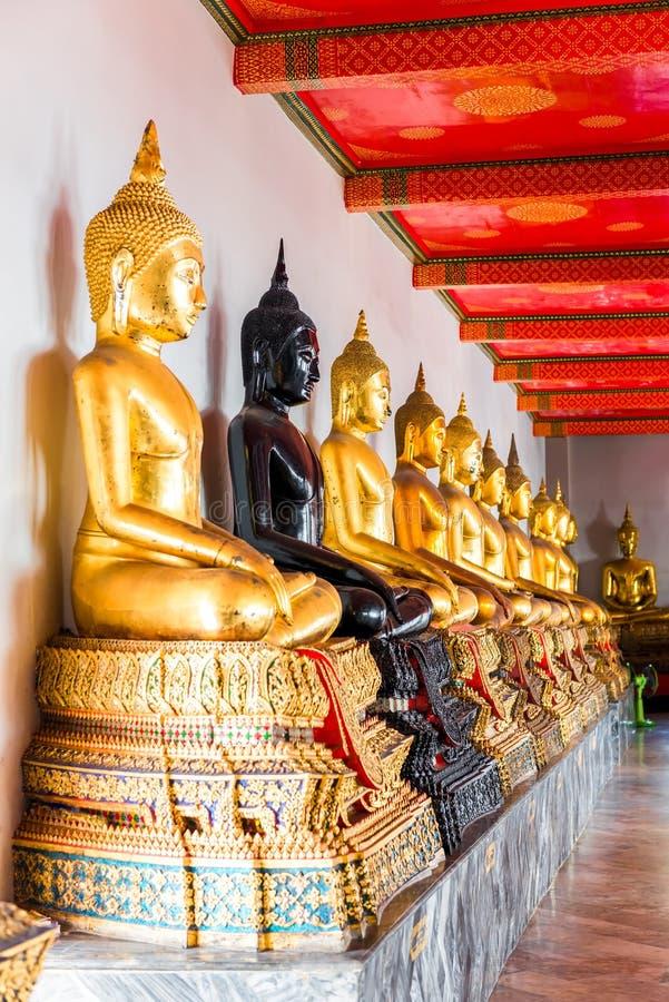 En serie av placerade Buddha i en thailändsk tempel arkivfoton