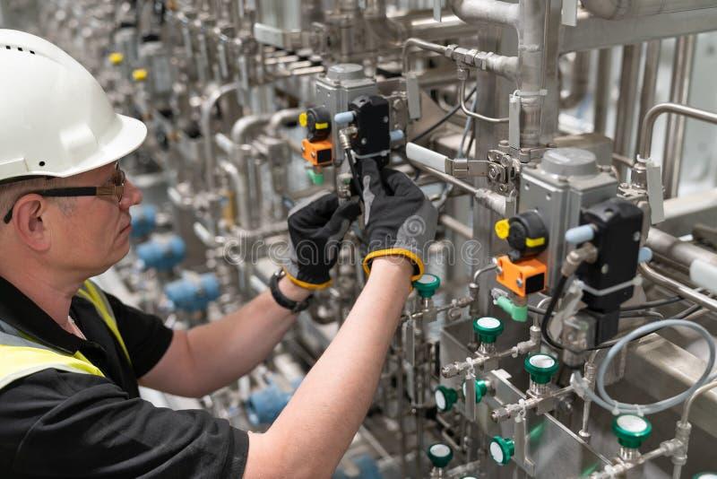 En servicetekniker kontrollerar en pneumatisk ventil royaltyfria foton