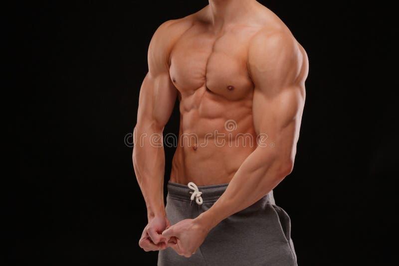 En sexig bodybuilder på en svart bakgrund Lättnad och skulpturala muskler av kroppen sund livsstil för begrepp royaltyfria bilder