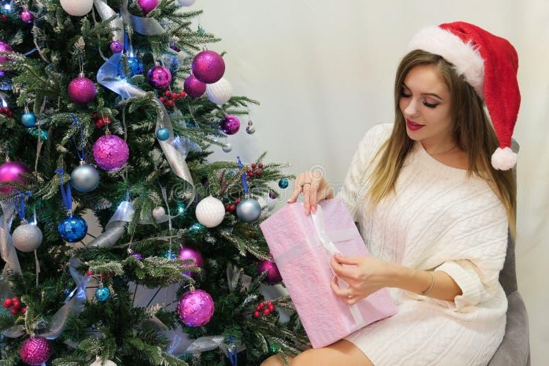 En sexig flicka i ett rött lock och en stucken tröja sitter bredvid julgranen Rosa ask med en gåva i deras händer Kvinnligt fingr fotografering för bildbyråer