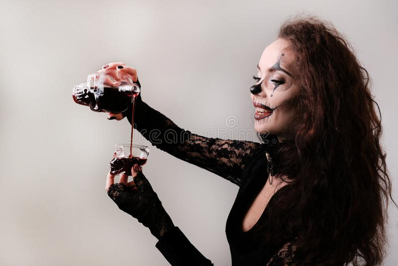En sexig härlig flicka i ett svart snör åt klänningen häller ett mörkt - röd flytande från en karaff in i ett exponeringsglas i f royaltyfri foto