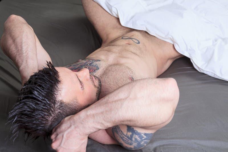 En sexig naken man lägger i sängen royaltyfria bilder