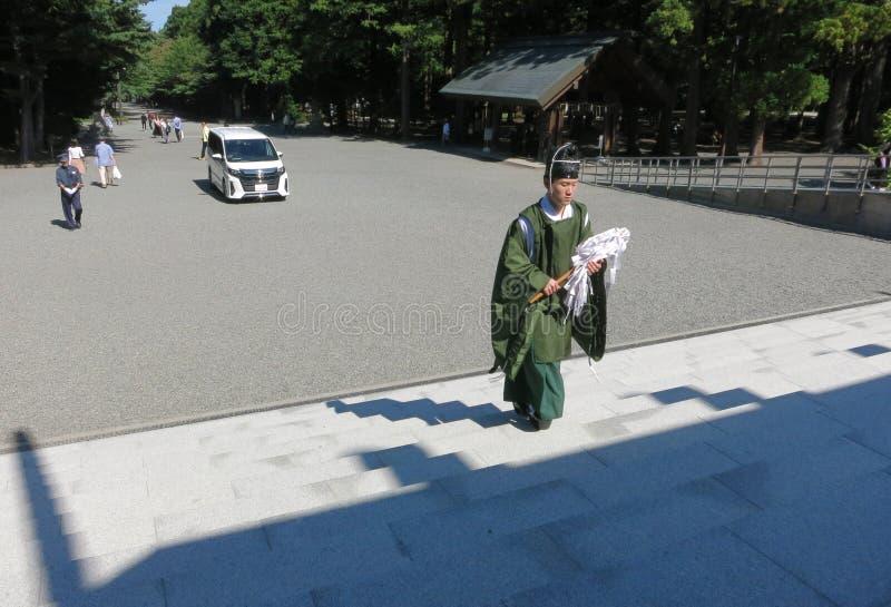 En shinto präst som bär ett grönt plagg, går upp trappan av en relikskrin, når han har välsignat en ny bil royaltyfria foton