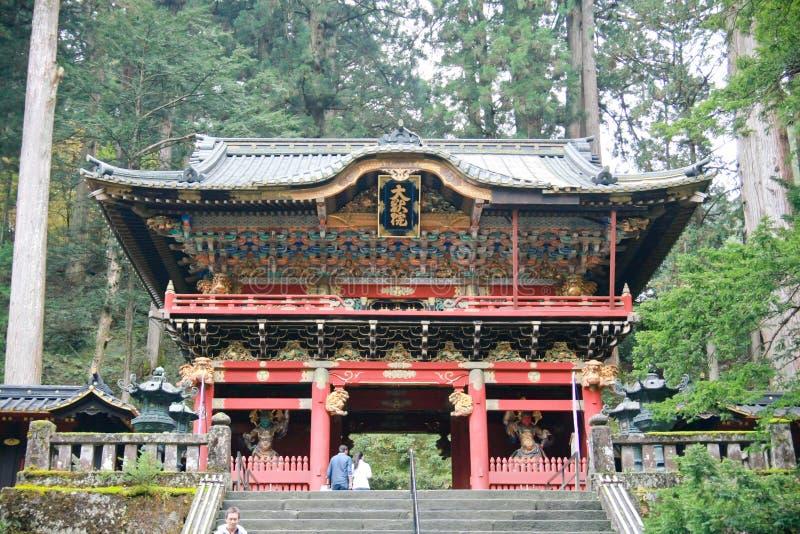 En shintopräst sopar under den Yomeimon porten på Nikko, Japan fotografering för bildbyråer
