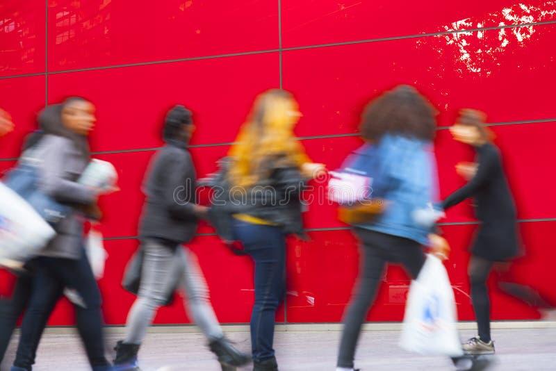 En shoppare som går mot den röda väggen arkivfoton